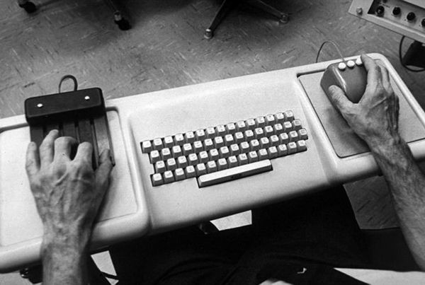 Two hands on an old keyboard, mouse on right and 4 button device on left